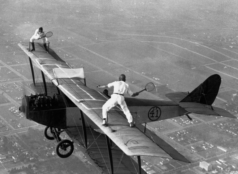 Gladys Roy and Ivan Unger playing a game of tennis on the wings of a biplane above Los Angeles in 1925.