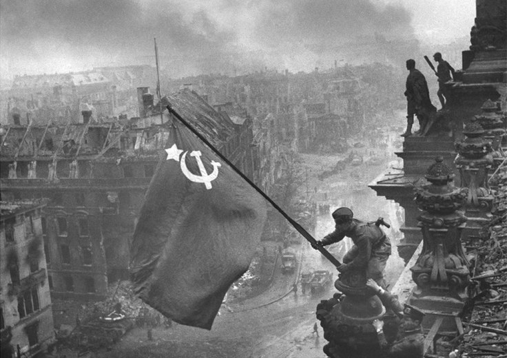 Red Army soldiers hoisting a hammer-and-sickle flag over the Reichstag in Berlin, 1945.